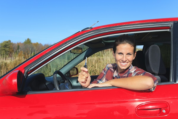 woman sitting in red car holding up car keys
