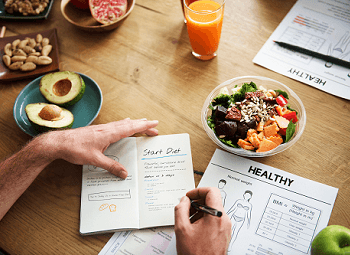 Man taking notes about eating healthy with several healthy foods around him on a table